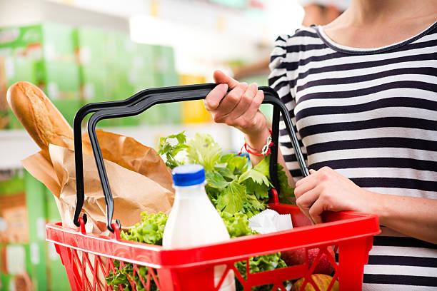 Full shopping basket Woman shopping at store with shopping basket. shopping basket stock pictures, royalty-free photos & images
