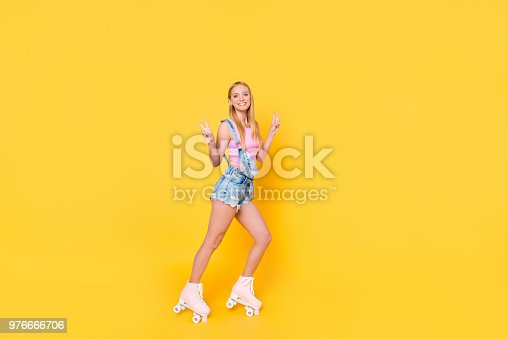 1092709104 istock photo Full size body portrait of attractive pretty girl riding on roller skates gesturing v-signs with two hands looking at camera isolated on yellow background 976666706