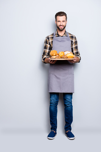 istock Full size body portrait of joyful cheerful baker in jeans, shoes, shirt, apron with stubble having, showing tray with bakery products, looking at camera, isolated on grey background 970412060