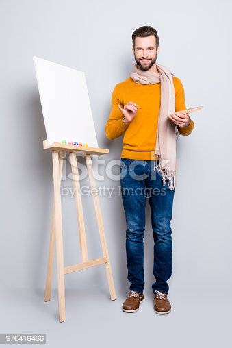 636761588istockphoto Full size body portrait of joyful trendy artist with scarf around neck, hairstyle, in jeans, sweater, holding colorful palette and brushes in hands, isolated on grey background 970416466
