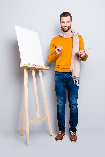636761588 istock photo Full size body portrait of joyful trendy artist with scarf around neck, hairstyle, in jeans, sweater, holding colorful palette and brushes in hands, isolated on grey background 970416466