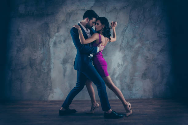 full size body portrait of lovely attractive couple standing close in tango position face to face dancing, charming lady in purple tight dress gentlemen in tux isolated on grey background movement - tango taniec zdjęcia i obrazy z banku zdjęć