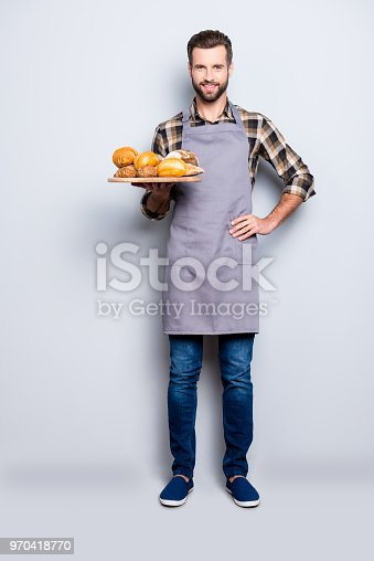 istock Full size body portrait of positive attractive baker in jeans, shoes, shirt, apron with stubble having tray with bakery products, looking at camera, isolated on grey background 970418770