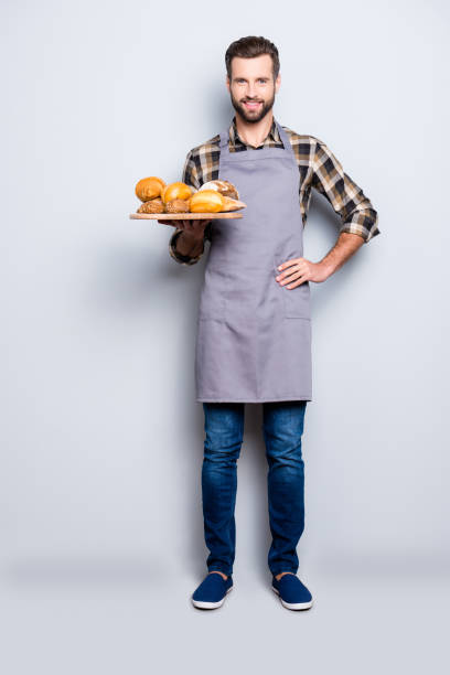 full size body portrait of positive attractive baker in jeans, shoes, shirt, apron with stubble having tray with bakery products, looking at camera, isolated on grey background - panettiere foto e immagini stock