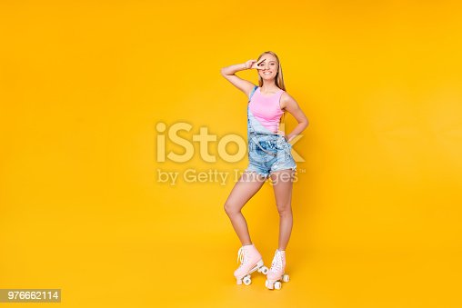 1092709104 istock photo Full size body portrait of pretty funky girl on roller skates gesturing v-sign near eye looking at camera isolated standing over yellow background 976662114