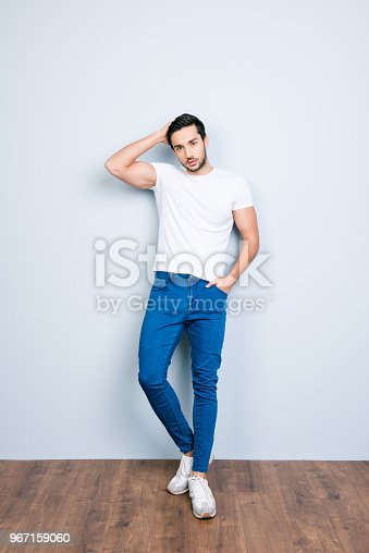 istock Full size body portrait of stunning brutal man touching his perfect smoth soft healthy hair holding hand in pocket flirting looking at camera standing over grey background 967159060