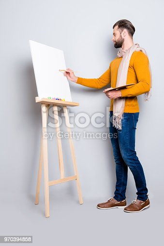 636761588istockphoto Full size fullbody portrait of busy creative artist with scarf around neck, hairstyle, in jeans, sweater, holding colorful palette and drawing a picture, isolated on grey background 970394858