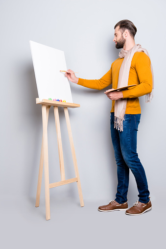 636761588 istock photo Full size fullbody portrait of busy creative artist with scarf around neck, hairstyle, in jeans, sweater, holding colorful palette and drawing a picture, isolated on grey background 970394858