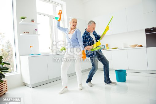 istock Full size, fullbody portrait of crazy foolish funny mad cool couple of senior dancing, singing, man playing on mop like guitar, woman holding spray in raised hand, positive people concept 966874488