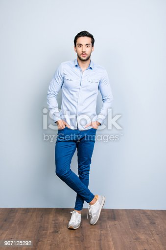istock Full size fullbody portrait of harsh cool bachelor with black hair holding two hands in pockets of jeans looking at camera standing over grey background 967125292
