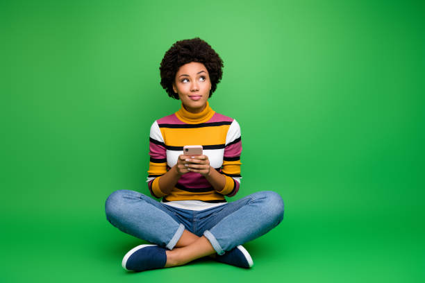 Full size photo minded afro american girl sit legs crossed folded use cell phone blogging think thoughts type social media post wear denim jeans clothes isolated green color background stock photo