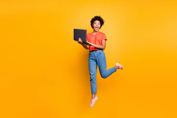 full size photo of amazed crazy curly brown hair girl use her laptop have notification in feednews jump scream omg wear denim jeans red t-shirt lifestyle sneakers isolated yellow color background - funky stock pictures, royalty-free photos & images
