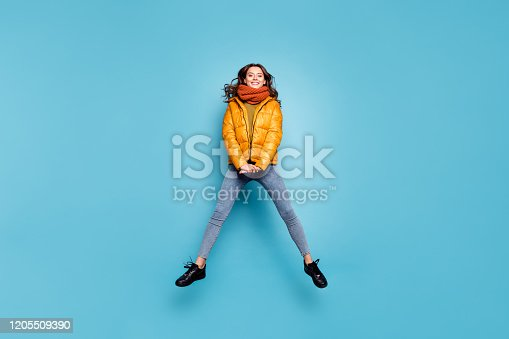 Full size photo of amazing cute model lady jumping high enjoy weekend relaxing walk, street playful wear stylish windbreaker jeans scarf sweater isolated blue color background