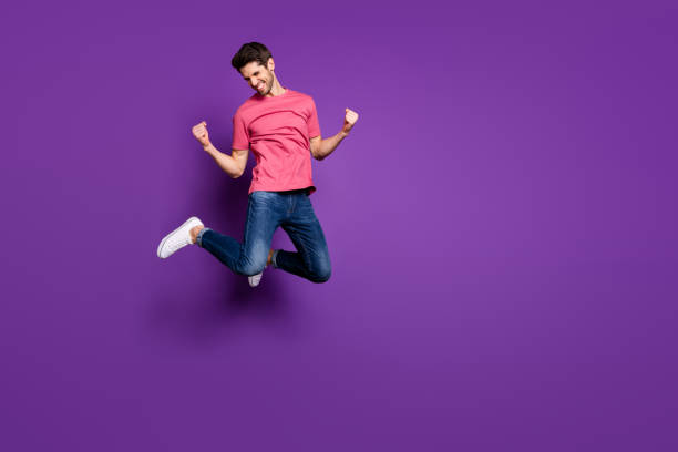 Full size photo of attractive guy jumping high up rejoicing best win sports bets bookmaker wear casual pink t-shirt jeans shoes isolated purple color background stock photo