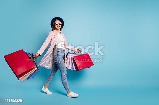 istock Full size photo of cute pretty cheerful lady in eyeglasses eyewear go shopping for bargains wear season cote denim jeans isolated over blue background 1171895329