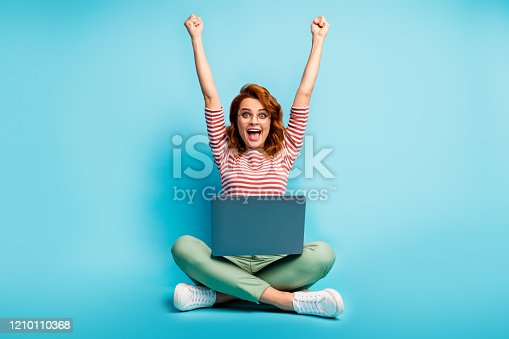 Full size photo of excited ginger hair woman sit floor legs crossed work laptop, finish start-up report scream yeah raise fists wear green white sweater footwear isolated blue color background