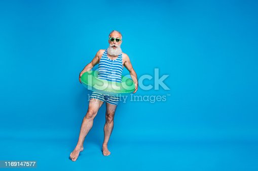 Full size photo of impressed man in eyeglasses eyewear wearing striped bathing costume hold lifesaver trying ocean water isolated over blue background