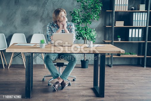 istock Full size photo of minded freelancer having thoughts sitting on chair wearing eyeglasses eyewear checkered plaid shirt trousers in loft 1165674280