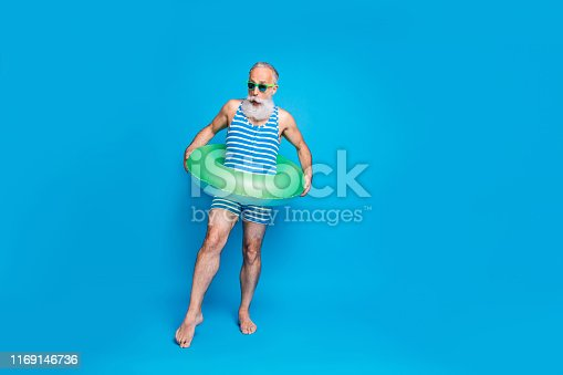 Full size photo of shocked man with rubber ring trying temperature of water screaming omg wearing eyeglasses eyewear isolated over blue background