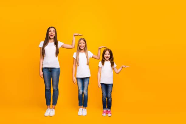 foto em tamanho completo de três irmãs irmã não acreditam que tal rápido crescimento até desgaste casual roupa isolada fundo amarelo - alto descrição geral - fotografias e filmes do acervo