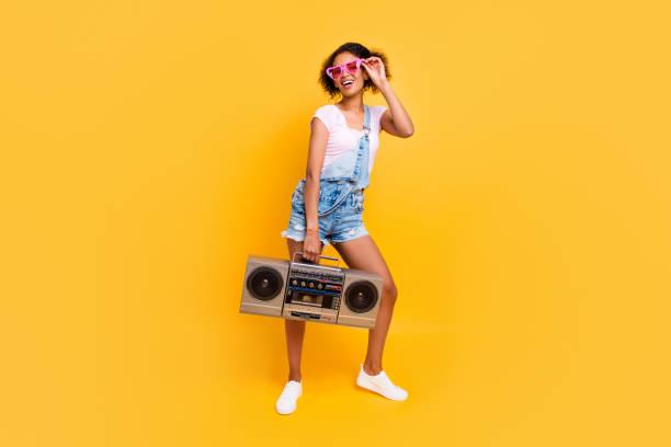 full-size porträt fröhliche positive mädchen in brille jeans insgesamt hält der boom-box in der hand gehen, um partei isoliert auf gelbem hintergrund. musik-liebhaber-fan-konzept - radio kultur stock-fotos und bilder