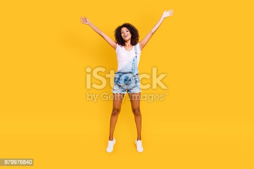 Full size portrait of funny crazy girl jumping in air holding hands up making star pose looking at camera isolated on yellow background. Luck success achievement concept