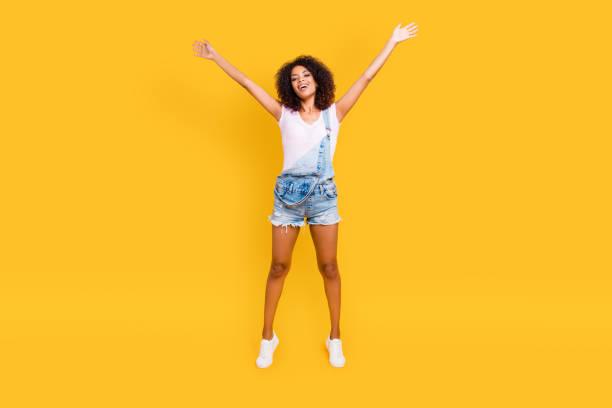 full-size portrait von lustiges verrücktes mädchen springen in luft, die hand in hand macht sterne pose, blick in die kamera auf gelbem hintergrund isoliert. erfolgskonzept erfolg glück - jeans overall stock-fotos und bilder