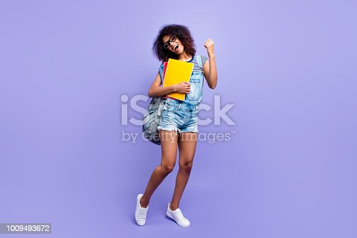 1009493672istockphoto Full size portrait of glad successful girl in jeans overall sneakers denim outfit celebrating pass exams holding textbooks isolated on violent background highschool high school 1009493672