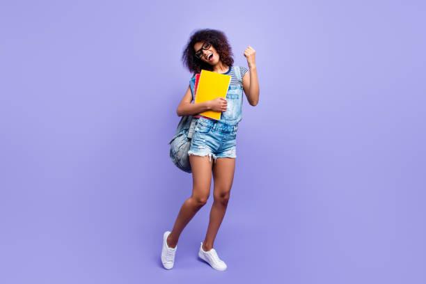 full-size-porträt von froh erfolgreiche mädchen in jeans insgesamt sneaker denim outfit feiern prüfungen halten lehrbücher isoliert auf gewalttätige hintergrund highschool highschool - jeans overall stock-fotos und bilder