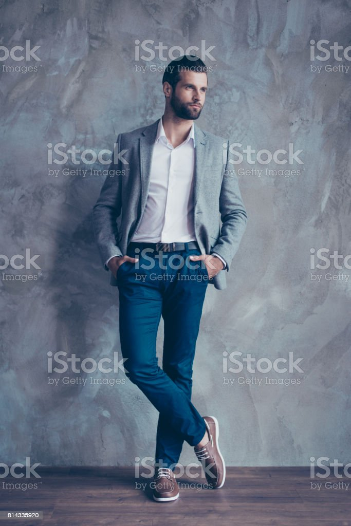 Full size portrait of stylish young bearded man standing on gray concrete background. He is in a suit, standing with crossed legs stock photo
