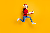 istock Full size profile photo of crazy little lady jumping high taking giftbox from santa in x-mas midnight wear red knitted pullover and jeans isolated yellow background 1179337267