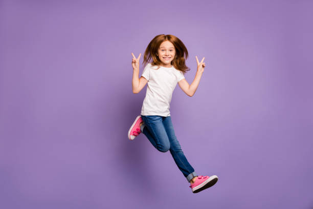 Full size profile photo of funky small foxy lady jumping high rejoicing walking street showing v-sign symbols wear casual white t-shirt jeans isolated purple background stock photo