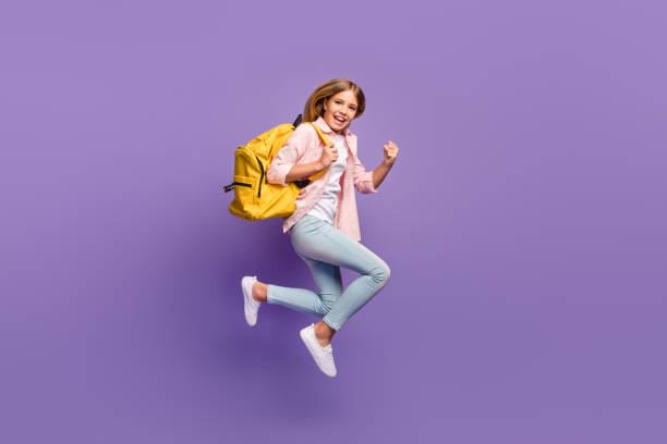 Full size profile photo of hooray pretty girl jump run wear pink shirt jeans sneakers rucksack isolated on violet background stock photo