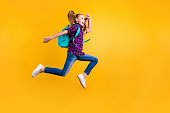 Full size profile photo of little pupil jump high holidays wear casual checkered, shirt jeans denim isolated yellow background