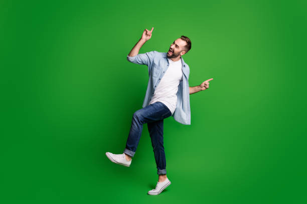 Full size profile photo of optimistic guy dancing wear blue shirt jeans footwear isolated on green color background stock photo