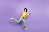 Full size profile side photo of cheerful excited wavy hair girl jump, run play catch-up game with friends on spring time wear yellow pullover green pants isolated violet purple color background