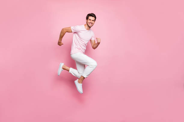 Full size profile side photo of content guy moving isolated over pink background Full size profile side, photo of content guy moving isolated over pink background jump shot stock pictures, royalty-free photos & images