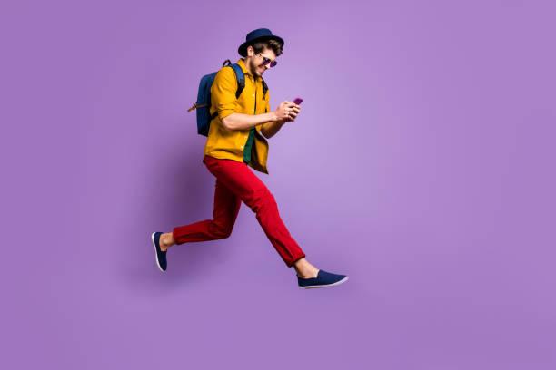 Full-Größe Profil Seite Foto von positiven Hipster Kerl Relax Trip Jump verwenden Smartphone-Suche Rabatte laufen schnell tragen gelb Shirt rote Hose Rucksack isoliert violett Farbe Hintergrund – Foto