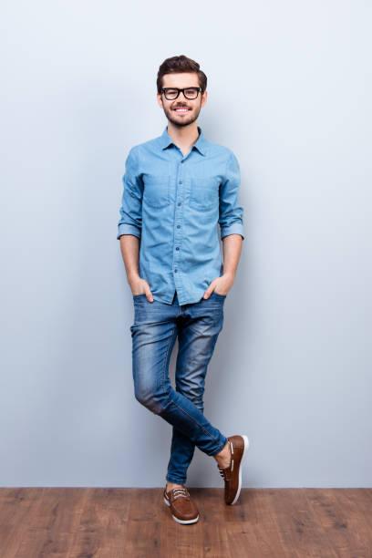 retrato vertical de tamaño completo de joven brunet alegre en ropa casual con estilo. él mira a cámara en fondo lifgt - un solo hombre joven fotografías e imágenes de stock