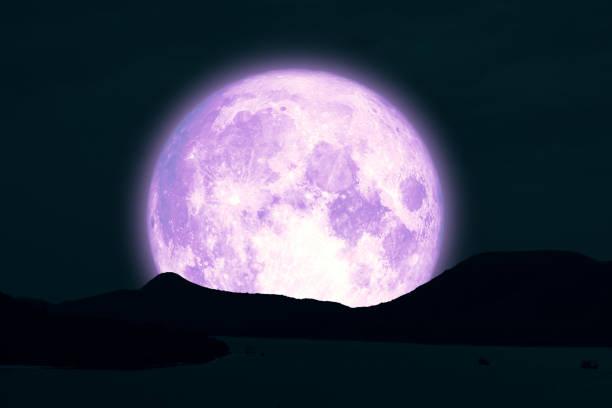 Full Snow Moon on night sky back silhouette island in the ocean night sky stock photo