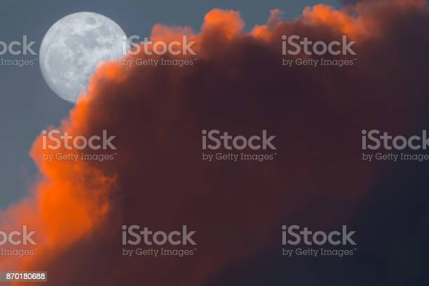 Photo of Full Snow Moon Rise peeking behind pink clouds during sunset