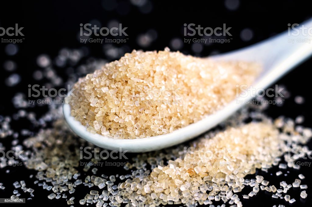 Full spoon of sugar isolated on black background. stock photo