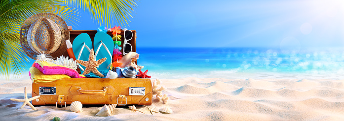 istock Full Suitcase With Accessories On Tropical Beach 1148071319
