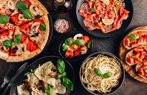 mesa completa de refeições italianas em pratos pizza, massas, ravióli, carpaccio. salada caprese e bruschetta de tomate no fundo preto. - comida italiana - fotografias e filmes do acervo