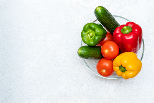 Full transparent bowl of low calorie whole vegetables red tomatoes, cucumbers, peppers on a light background, top view, copy space. Vegetarian, dietary, healthy food.