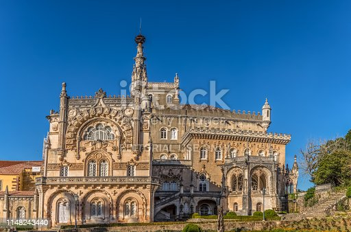 Luso / Aveiro / Portugal - 03 09 2019 : Full view of the back facade of the Bussaco Palace, neo gothic monument, with gardens and blue sky, in Portugal