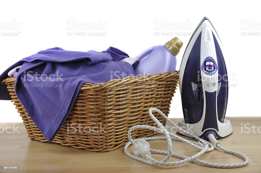 A full wicker laundry basket on a table next to an iron stock photo