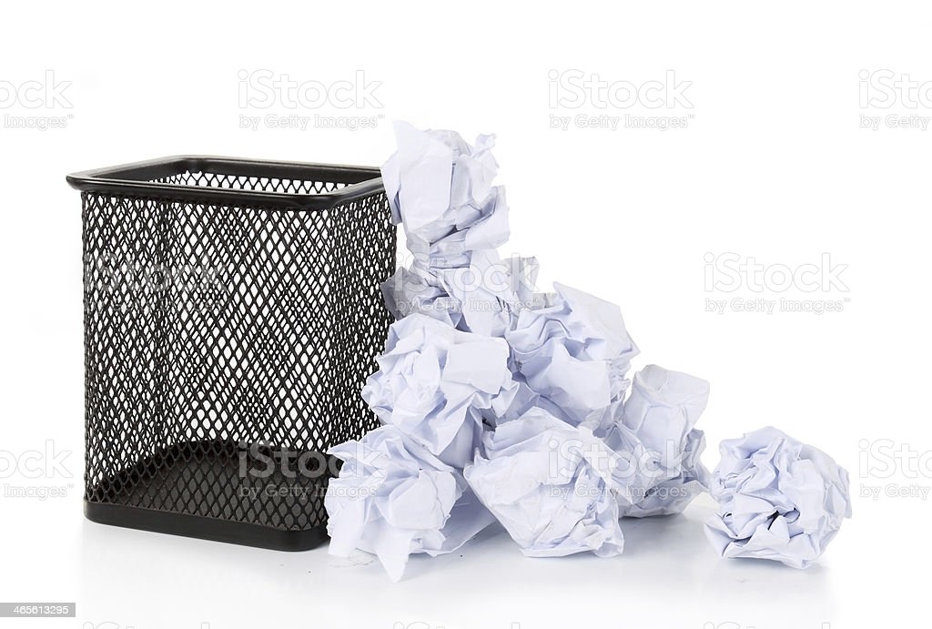 Full wire mesh trash can with crumpled paper scattered around. royalty-free stock photo