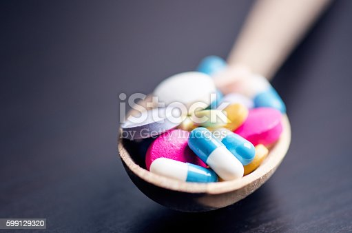 istock Full wooden spoon of pills. Pharmacy background 599129320