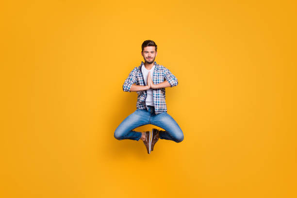 Full-body portrait of levitates in the air meditating and concen Full-body portrait of levitates in the air meditating and concentrating isolated on shine yellow background yogi stock pictures, royalty-free photos & images